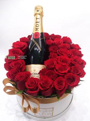 Šampanjac i ruže u ukrasnoj kutiji.
