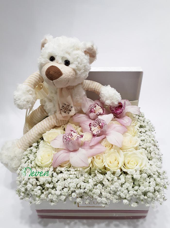 Plišani medvedić u kutiji sa ružama i orhidejama.